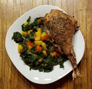 kale peppers turkey leg on white plate